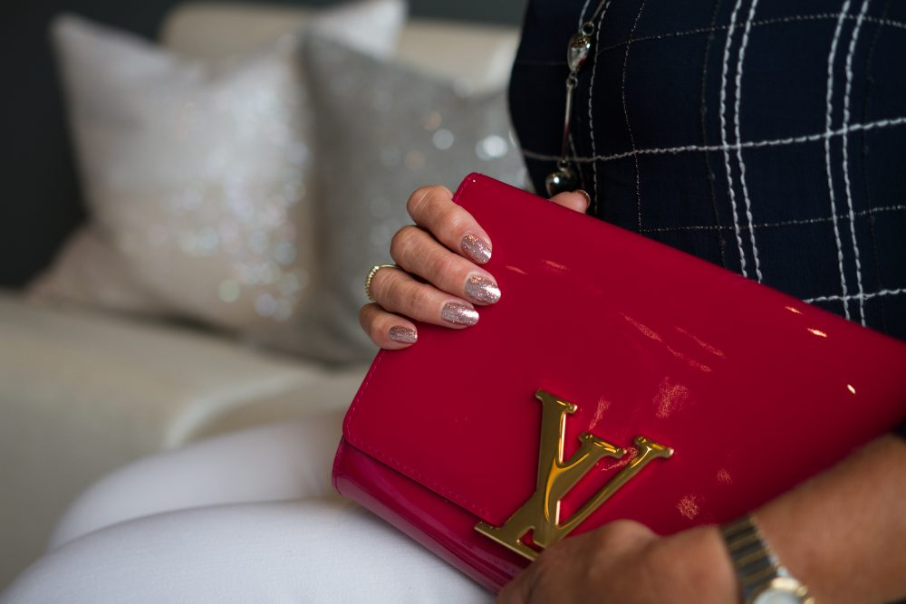 a client with glittery gel nails, holding her louis vuitton patent red clutch
