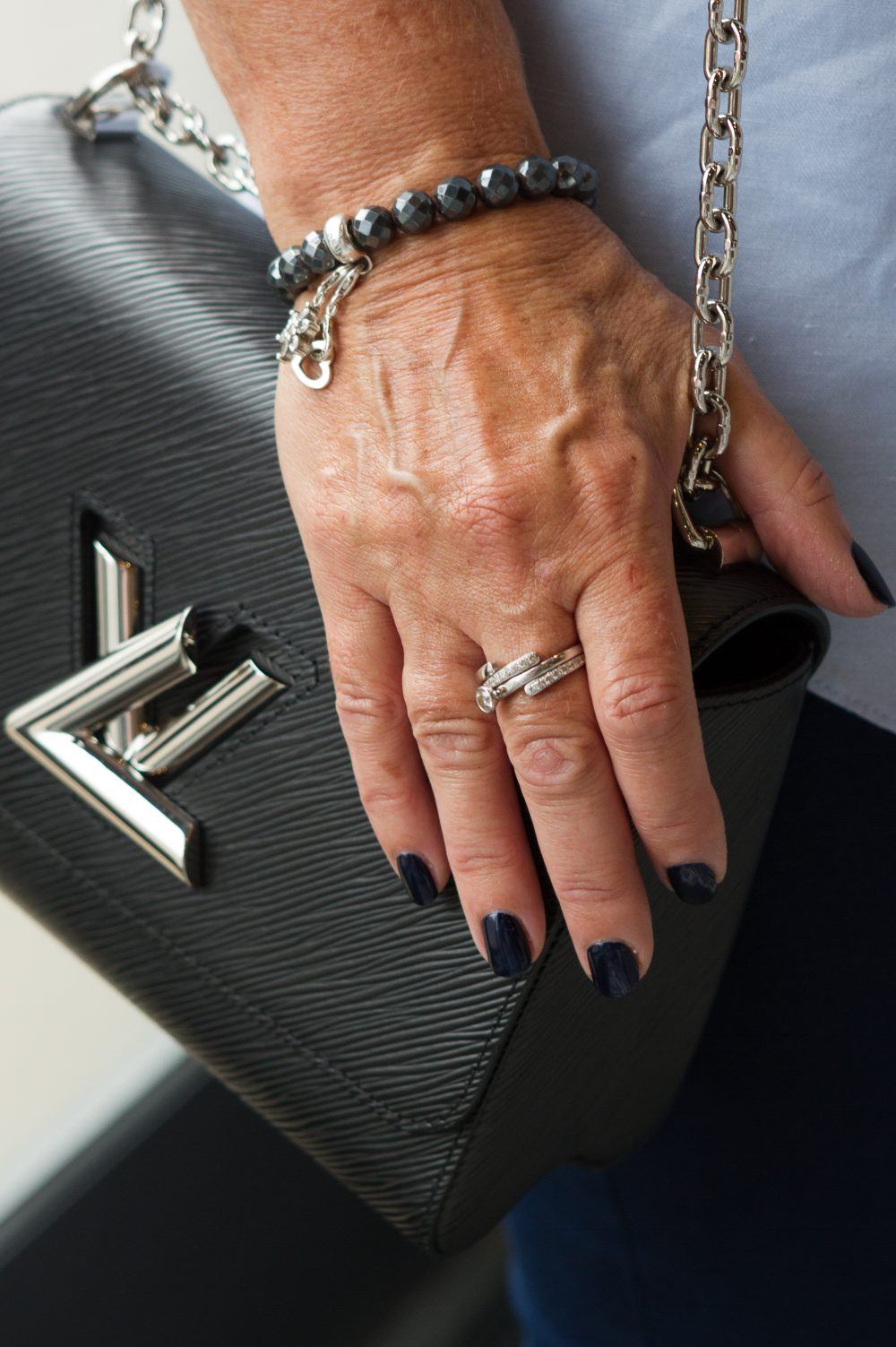 A clients nails in navy blue with an expensive hand bag
